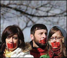 Protesters with red tape over their mouths.