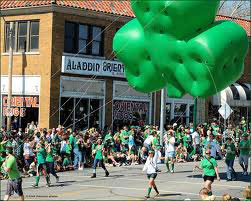 A group of people walking in the Kansas City Saint Patrick's Day parade .